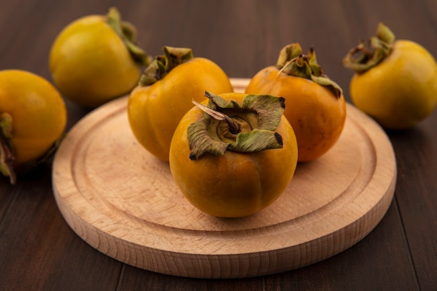Top view of fresh organic persimmon fruits on a wooden kitchen board on a wooden table