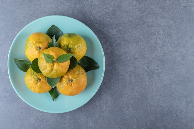 Top view of fresh organic tangerines on blue plate.