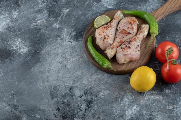 Vista dall'alto pomodori biologici freschi e limone con cosce di pollo crude su sfondo grigio.