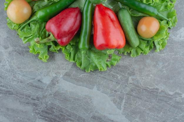 Vista dall'alto di verdure biologiche fresche su sfondo grigio.