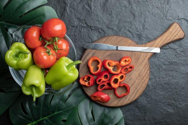Vista dall'alto di verdure biologiche fresche, peperoni rossi a fette su tagliere di legno e pepe e pomodori in una ciotola su sfondo nero.