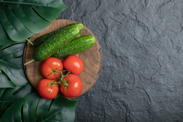 Top view of fresh organic vegetables on wooden board over black background.