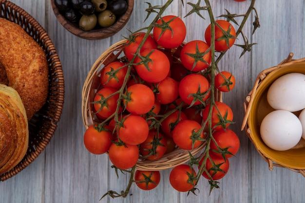 Vista dall'alto di pomodori a grappolo freschi biologici su un secchio con olive su una ciotola di legno e uova su un cesto su uno sfondo di legno grigio