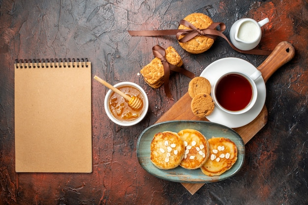 Top view of fresh pancakes a cup of black tea on a wooden cutting board honey stacked cookies milk and spiral notebook on a dark surface