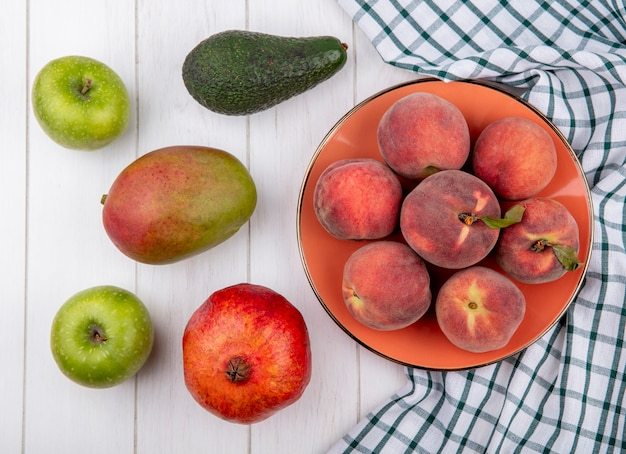 Top view of fresh peaches on bowl on checked tablecloth with apples mango pomegranate isolated on white