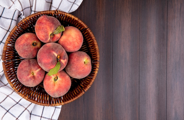 Top view of fresh peaches on bucket on checked tablecloth on wood with copy space