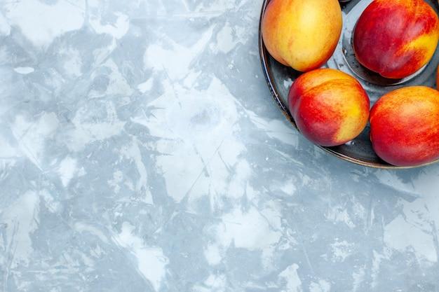 Vista dall'alto pesche fresche deliziosi frutti estivi sulla scrivania bianca chiara