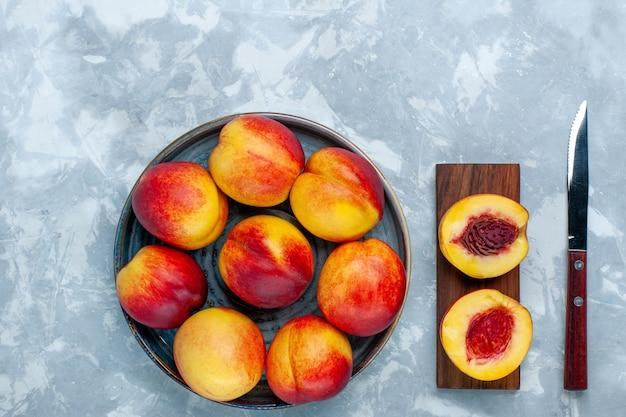明るい白い机の上に新鮮な桃のおいしい夏の果物の上面図