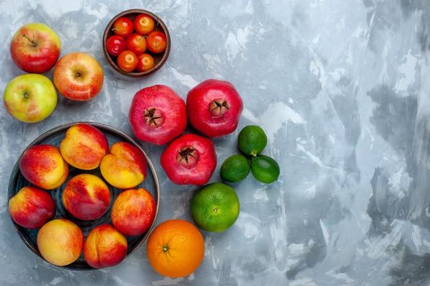 Вид сверху свежие персики, вкусные летние фрукты со сливами и яблоками на светло-белом столе