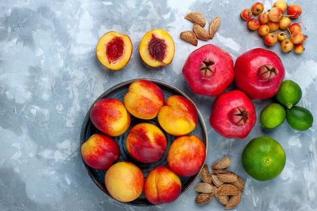 Vista dall'alto pesche fresche deliziosi frutti estivi con mandarini e limone sulla scrivania bianco chiaro