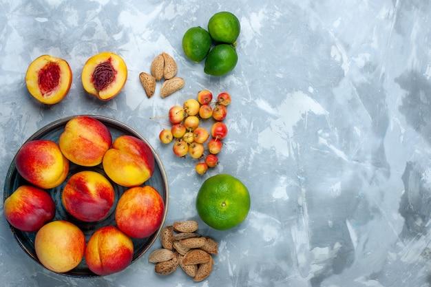 Вид сверху свежие персики вкусные летние фрукты с мандаринами на светло-белом столе