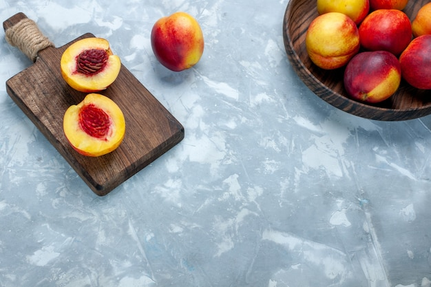 Вид сверху свежие персики, спелые и вкусные фрукты внутри коричневой тарелки на светло-белой поверхности