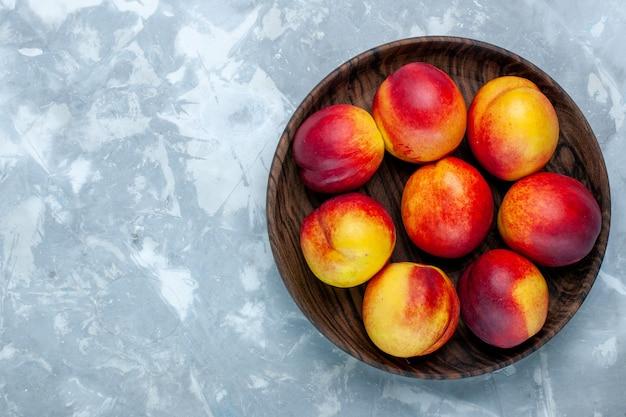 Вид сверху свежие персики, спелые и вкусные фрукты внутри коричневой тарелки на светло-белом столе