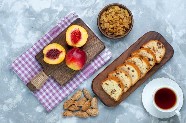 真っ白な机の上にケーキやレーズンと一緒に新鮮な桃のまろやかでおいしい果物の上面図
