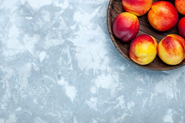 Vista dall'alto pesche fresche frutta pastosa e gustosa all'interno del piatto marrone sulla scrivania bianco chiaro