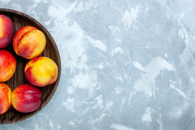 Top view fresh peaches mellow and tasty fruits inside brown plate on light white desk