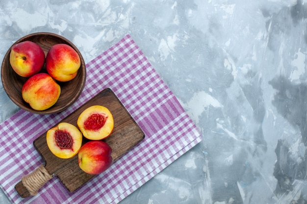 Top view fresh peaches mellow and tasty fruits inside brown plate on the light white surface