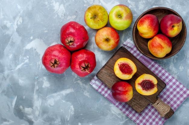 Vista dall'alto pesche fresche frutta pastosa e gustosa con mele sulla scrivania bianca leggera