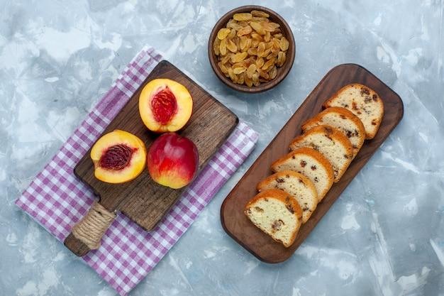 Vista dall'alto pesche fresche frutta dolce e gustosa con torte e uvetta sulla scrivania bianco chiaro
