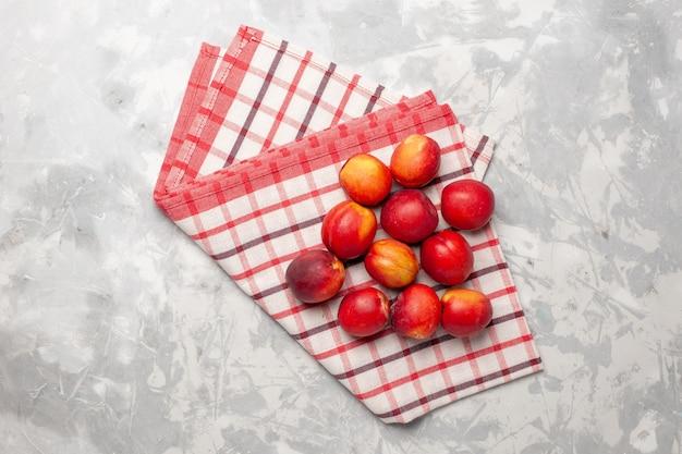 白い机の上に赤いトップビューの新鮮な桃
