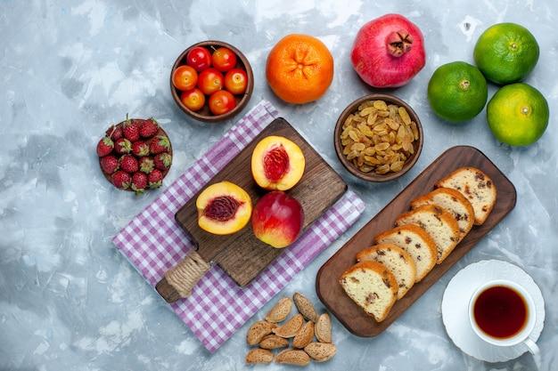 明るい白い机の上にケーキフルーツとレーズンと新鮮な桃の上面図