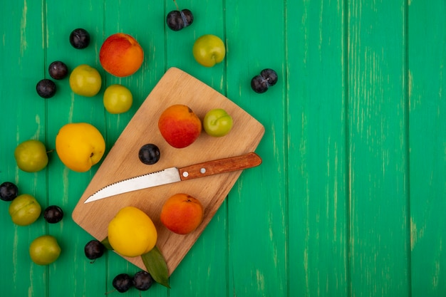 Top view of fresh peaches on a wooden kitchen board with knife on a green background with copy space