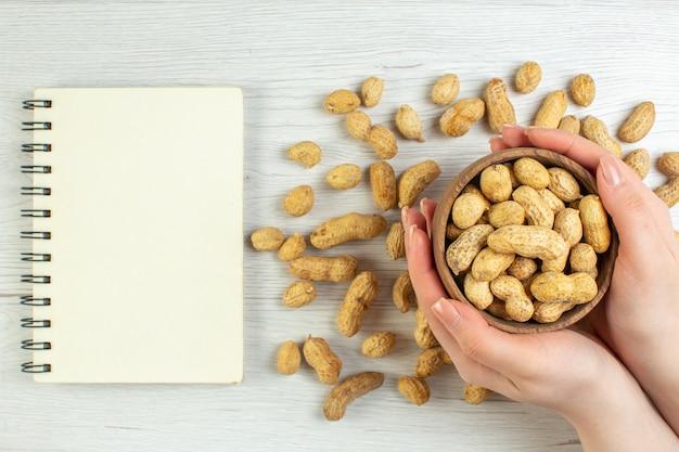 上面図白いテーブルの上の新鮮なピーナッツシネマフォトナッツカラームービーシードスナック