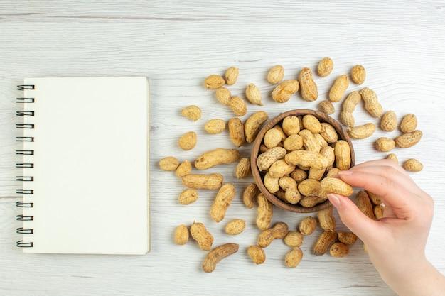 白いテーブルにメモ帳付きのトップビューの新鮮なピーナッツ