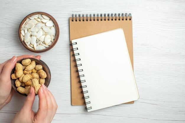 Вид сверху свежий арахис с белыми семенами на белом столе