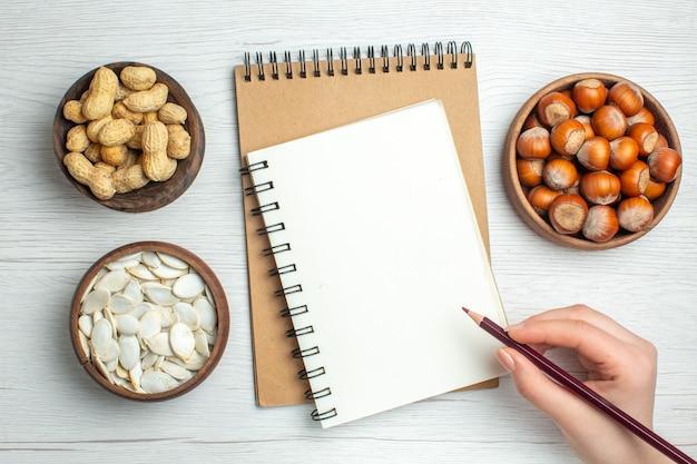 白いテーブルの上の白い種と新鮮なピーナッツの上面図