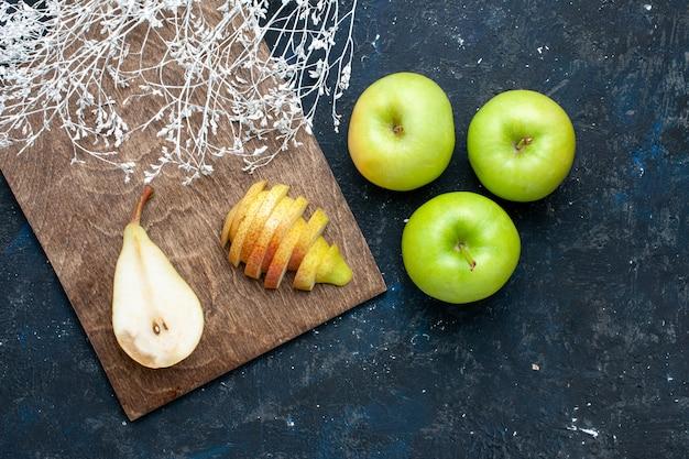 Vista dall'alto di pere fresche intere affettate e dolci con mele verdi sulla scrivania blu scuro, frutta fresca e morbida salute alimentare