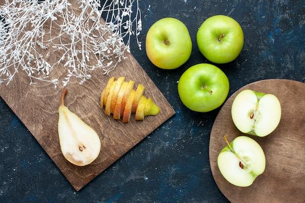 Vista dall'alto di pere fresche intere affettate e dolci con mele verdi sulla scrivania scura, frutta fresca e morbida salute alimentare