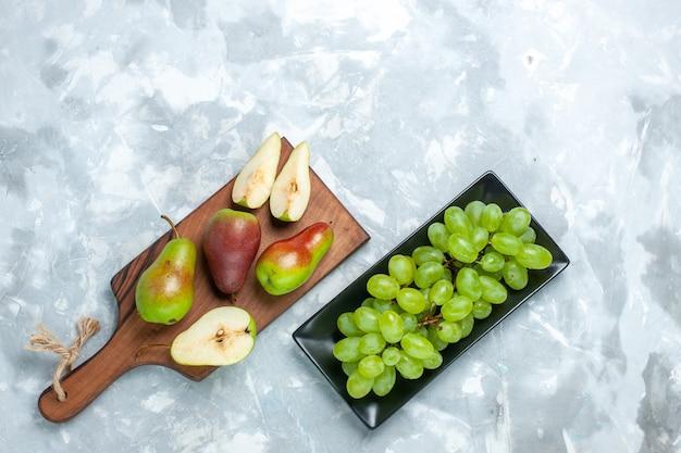 Vista dall'alto pere fresche con uva verde su sfondo bianco chiaro.