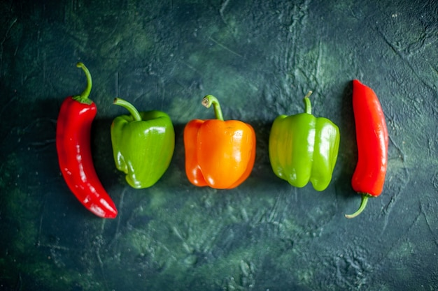 Vista dall'alto peperoni freschi su sfondo blu scuro peperoncino salsa di verdure foto a colori cibo spezia