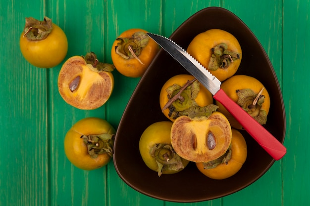 Top view of fresh persimmon fruits on a bowl with knife on a green wooden table