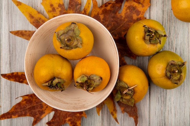Top view of fresh persimmon fruits on a bowl with leaves on a grey wooden table