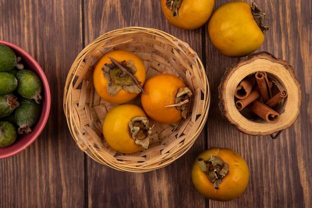 Vista dall'alto di cachi freschi frutti su un secchio con bastoncini di cannella su un barattolo di legno su uno sfondo di legno