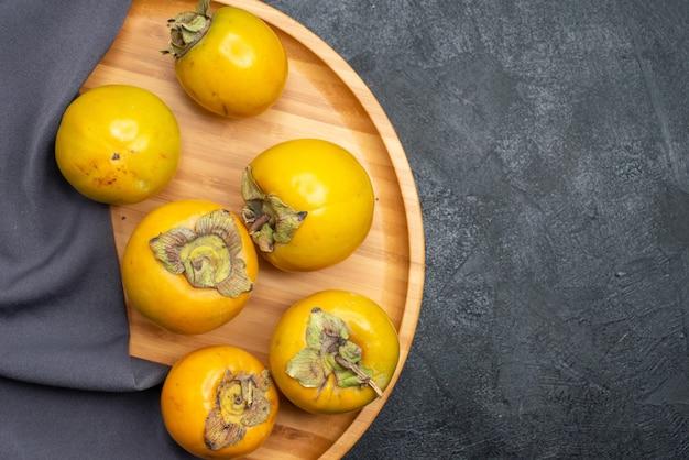 Vista superiore cachi freschi frutti dolci maturi sulla tavola scura frutta mellow maturo