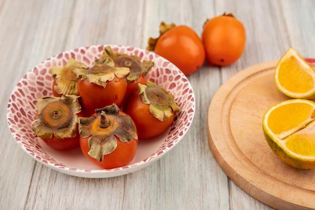 Vista dall'alto di cachi freschi su una ciotola con i mandarini su una tavola da cucina in legno su una parete di legno grigia