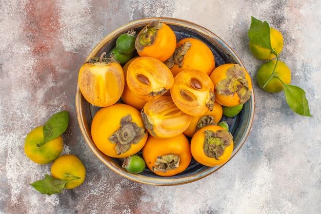 Vista dall'alto feykhoas di cachi freschi in una ciotola e mandarini su sfondo nudo