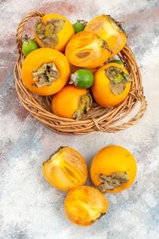 ヌードの背景に籐のバスケットに新鮮な柿feykhoasの上面図
