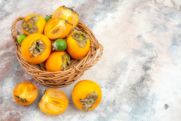 Top view fresh persimmons feykhoas in wicker basket on nude background