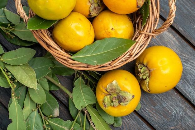 木製のテーブルのバスケットの中の新鮮な柿の上面図、果物は熟したまろやか