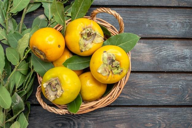 Vista dall'alto cachi freschi all'interno del cestello sul tavolo di legno, frutta matura matura