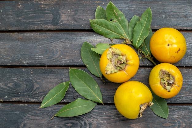 木製の素朴なテーブルの上のビュー新鮮な柿、熟した果実のまろやか