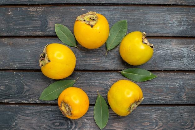 木の素朴な床のフルーツまろやかな熟した上から見た新鮮な柿