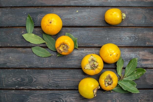 木製の素朴なテーブル、果物の熟したまろやかな上から見た新鮮な柿