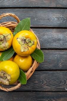 木の素朴な床のフルーツまろやかな上から見た新鮮な柿熟した甘い果物