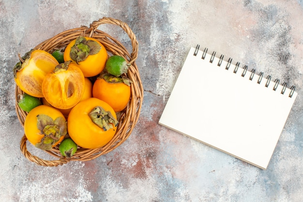 Top view fresh persimmons in wicker basket a notebook on nude background