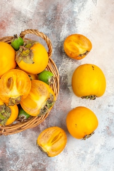 Top view fresh persimmons in wicker basket on nude background